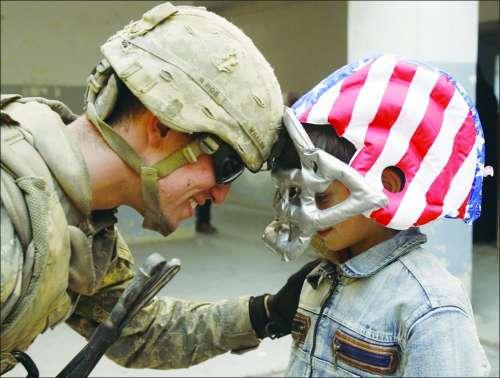 伊拉克 战争/美军撤出伊拉克前,一位美军士兵和头戴玩具橄榄球头盔的伊拉克...